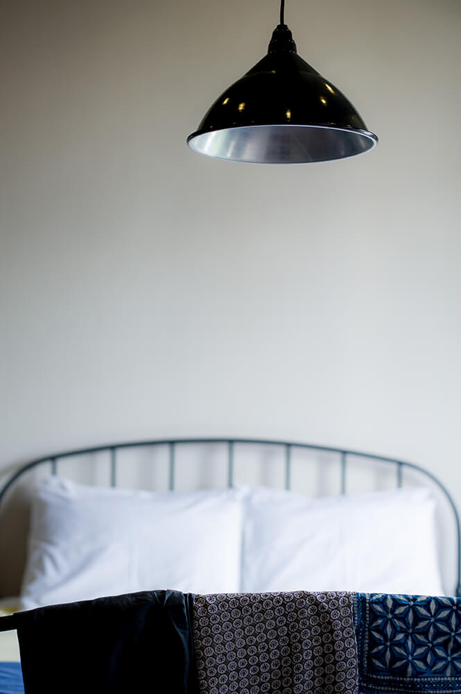 a pendant light suspended over the end of a double bed